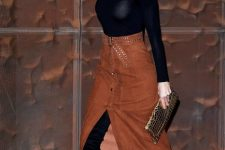 With black shirt, metallic clutch and high boots