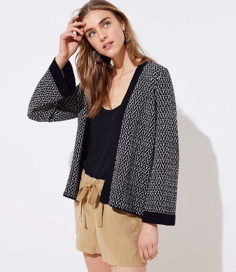With black top and beige belted shorts