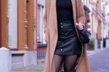 With black turtleneck, ankle boots and chain strap bag