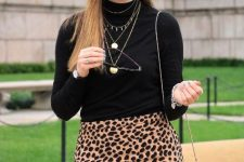 With black turtleneck, leopard printed skirt and unique bag
