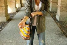 With brown hat, white t-shirt, olive green long jacket and printed bag