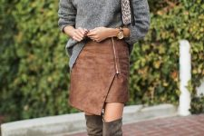 With gray loose sweater, printed clutch and suede over the knee boots