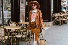 With labeled t-shirt, leather jacket, brown hat, straw bag and silver shoes