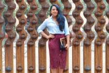 With light blue shirt, leopard printed bag and beige shoes