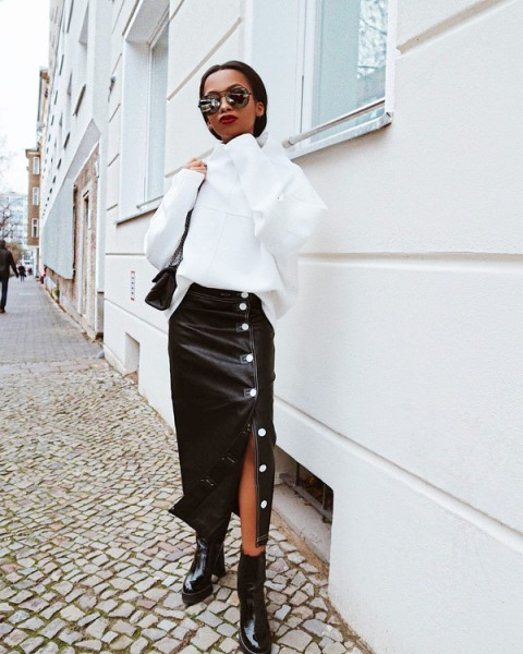 With white loose sweater, black bag and black patent leather boots