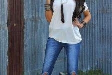 With white loose t-shirt, black vest and brown boots