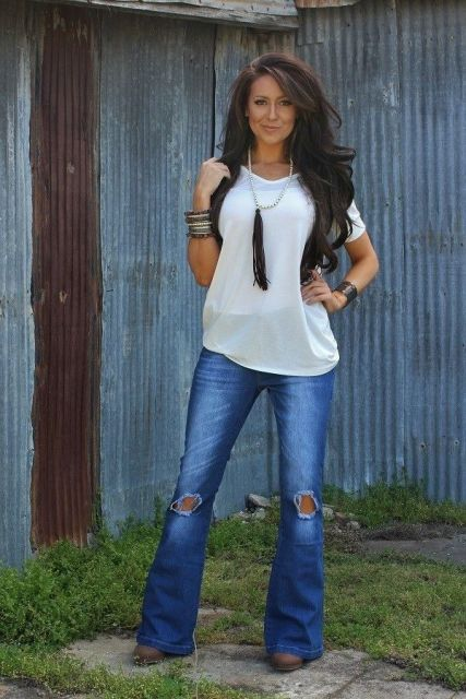 With white loose t shirt, black vest and brown boots