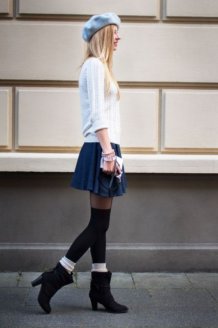 With white sweater, navy blue mini skirt and black boots