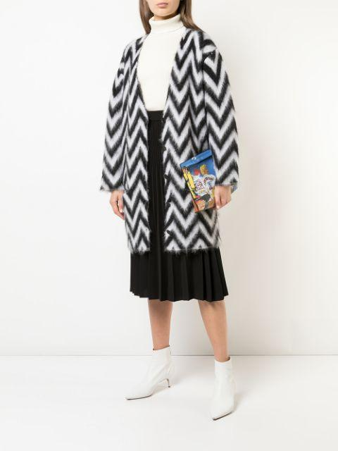 With white turtleneck, black pleated midi skirt, printed clutch and white ankle boots