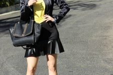 With yellow shirt, bomber jacket, black bag and sandals