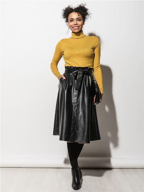 With yellow turtleneck, clutch and black boots