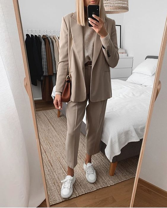 a beige suit with cropped pants, a matching top, white sneakers and a brown bag