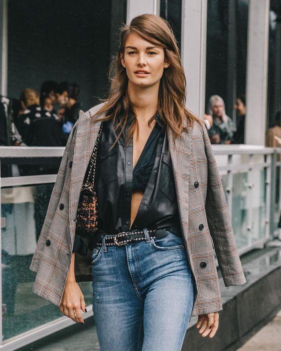 a black bra, a black leather shirt, a plaid blazer, blue jeans and a baguette printed bag