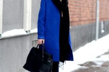 a black hoodie, black skinnies, white trainers, a black bag and an electric blue knee coat for a bold touch