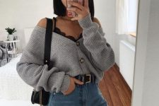 a black lace bralette, a grey cardigan tucked into blue jeans and a black bag for a relaxed and sexy look