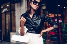 a black leather shirt, creamy pants, a creamy bag of a quirky shape for a unique and trendy look