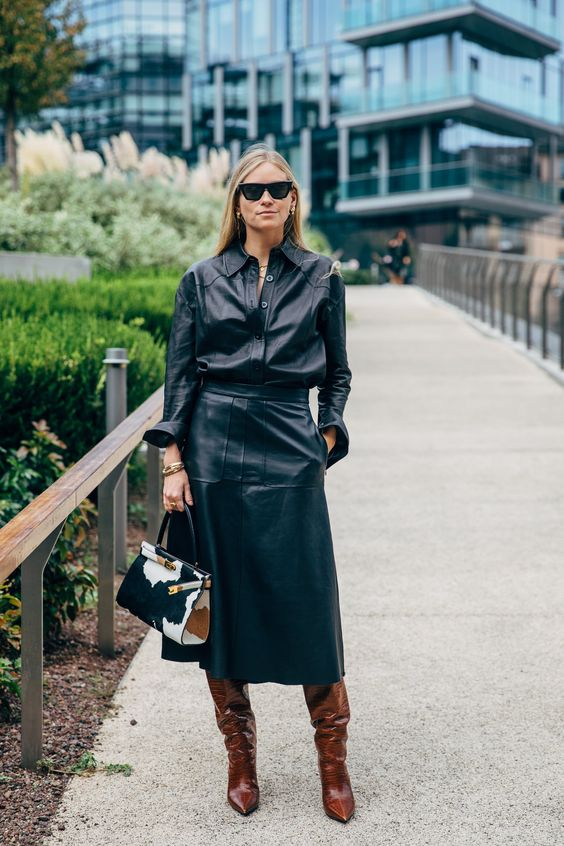 a black leather shirt plus an A-line leather midi, brown boots and a bold printed bag