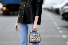 a black leather shirt with large lapels, blue jeans, sock boots and a shiny metallic mini bag