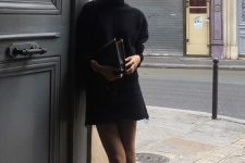 a black oversized sweater, a black denim mini, black square toe booties and a vintage clutch