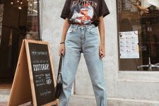 a black printed t-shirt, light blue high waisted straight jeans, white booties and a black bag