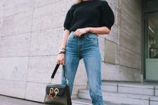 a black puff sleeve top, blue jeans, black pointed toe booties and a black bag for a wow effect