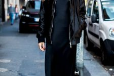 a black satin midi dress, a black lacquer bomber jacket, white heeled booties and statement earrings