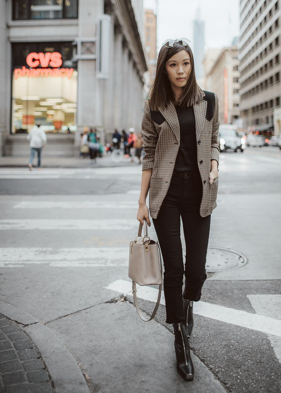a black tee, black cropped jeans, black booties with zips accenting them and a creamy bag plus a two tone tweed blazer