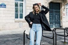 a black top, a black blazer, blue straight leg jeans, white booties and a white bucket bag