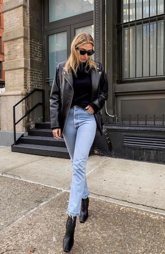 a black turtleneck, blue mom jeans, a black leather jacket and black square toe booties