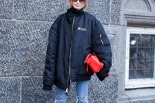 a black turtleneck, blue ripped jeans, a black oversized bomber jacket, bold blue booties and a red bag