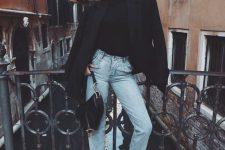 a black turtleneck, light blue jeans, white trainers, a black tux and a black baguette bag