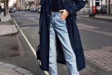 a black turtleneck, light blue raw hem jeans, brown reptile skin booties, a navy denim trench and a black bag