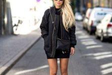 a black turtleneck mini dress, a black oversized bomber jacket, a crossbody and platform shoes