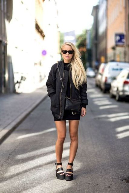 a black turtleneck mini dress, a black oversized bomber jacket, a crossbody and platform shoes