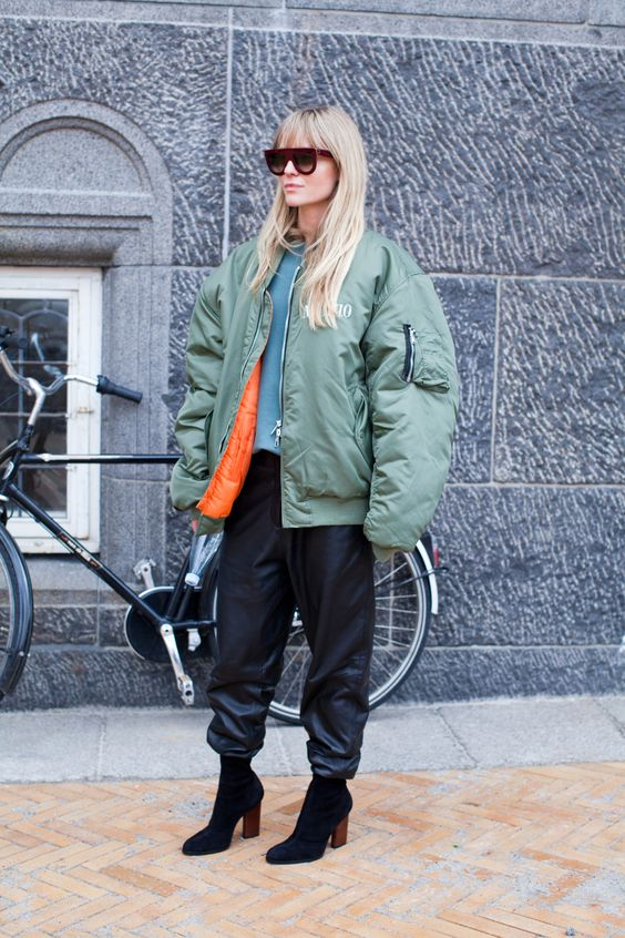 a blue top, leather pants, black suede sock booties and an oversized green bomber jacket