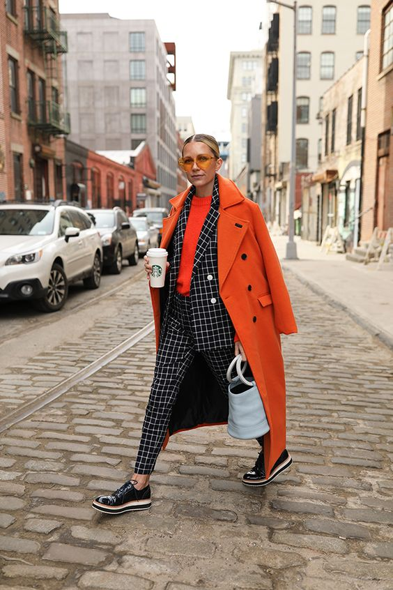 a bold look with an orange top, a windowpane suit, black platform shoes and a statement orange coat