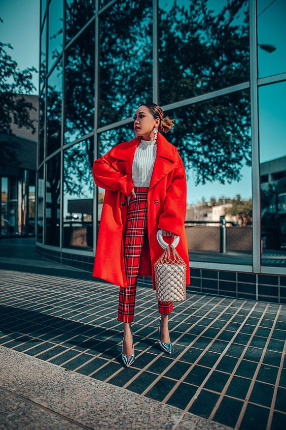 a bold outfit with a white knit crop top, plaid pants, silver shoes, an oversized red coat and a bucket bag