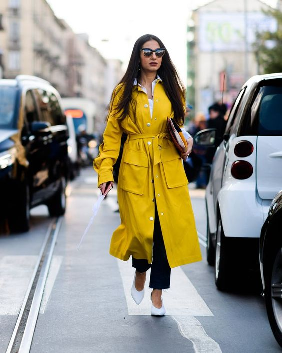 a bright fall look with a white shirt, navy jeans, white vintage-inspired shoes and a lemon yellow trench plus a clutch