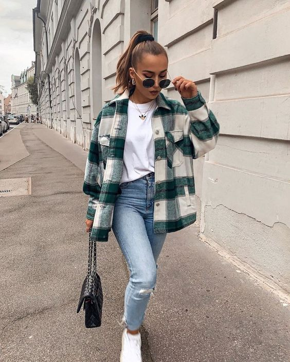 a casual look with a white tee, blue ripped jeans, white trainers, a plaid shirt jacket, a black bag