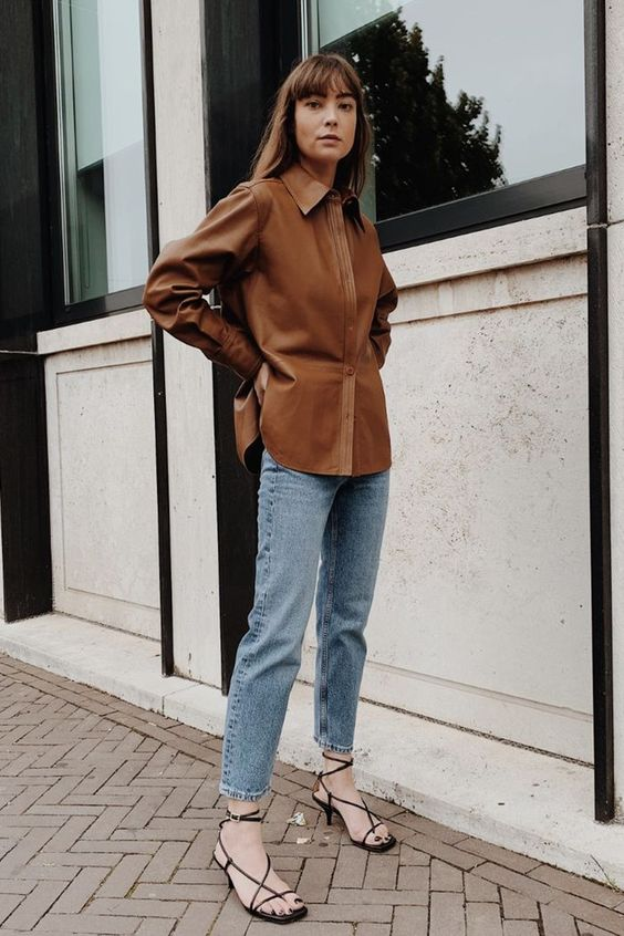 a chic fall look with a brown leather shirt, blue jeans, black square toe heels is easy to compose