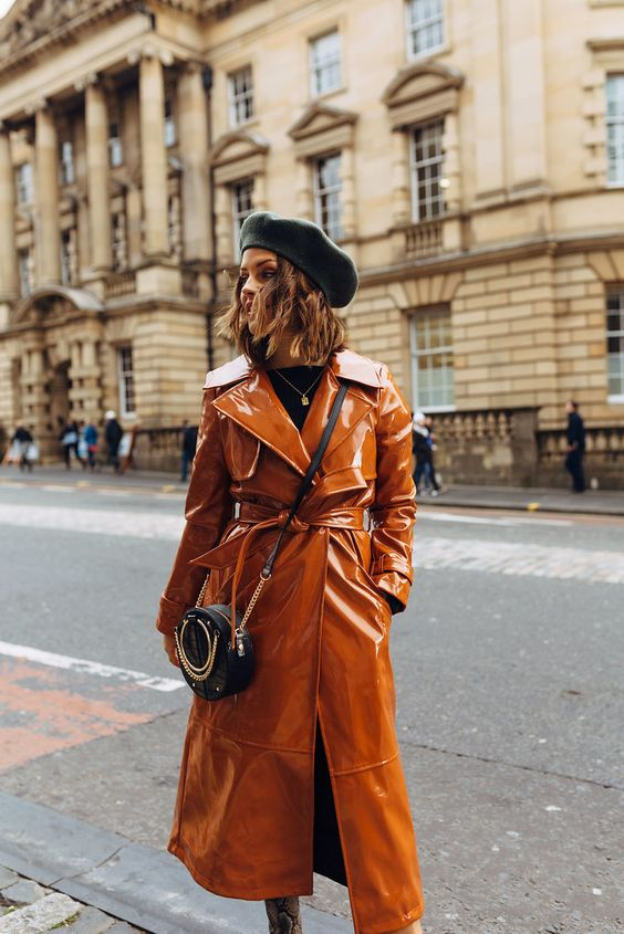 a chic fall outfit with a rust-colored lacquer trench, a black chain crossbody and a black beret