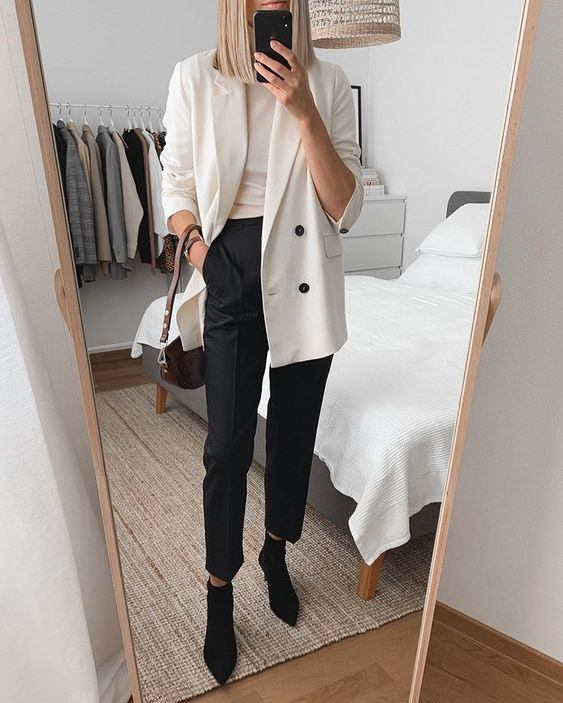 a chic monochromatic outfit with a creamy top and an oversized blazer, black pants and sock boots and a two tone bag