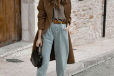 a comfy fall outfit with a brown top, light blue slouchy jeans, snake print booties, a brown coat and a beanie