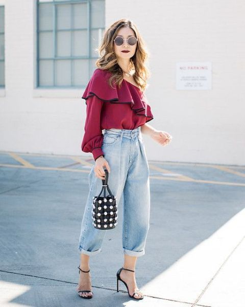 a fall party look with a purple one shoulder top, slouchy jeans, black heels and a bucket bag with pearls