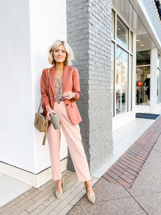 a fresh and lively outfit with a printed top, light pink pants, a rust colored blazer, grey shoes and a tan bag