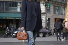 a graphite grey turtleneck, a navy tux, light blue jeans with a raw hem, black booties and a brown woven bag