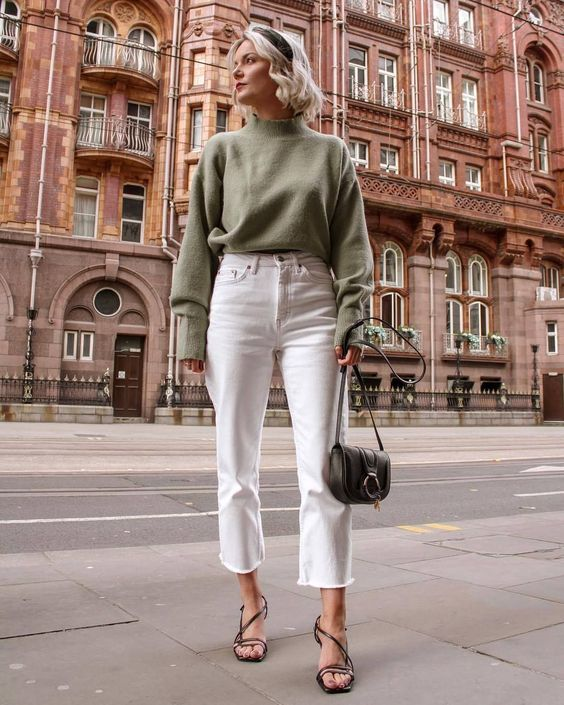 a green sweatshirt, white straight leg jeans, black strappy sandals and a black mini bag