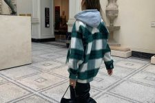 a grey hoodie, a green plaid shirt jacket, black leather pants, white sneakers and a black baguette bag