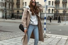 a grey hoodie, blue jeans, white ankle boots, a tan trench and a black bag