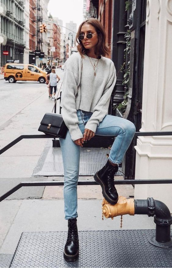a grey oversized cropped sweater, light blue mom jeans, black boots and a black bag